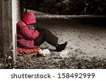 A Woman Sitting Against A Bric...