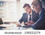 Small photo of Image of two young businessmen using touchpad at meeting