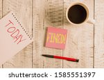 Small photo of Writing note showing Fined. Business photo showcasing clarify beer by causing precipitation of sediment during production Stationary placed next to a cup of black coffee above the wooden table.