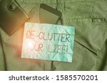 Small photo of Text sign showing De Clutter Your Life. Conceptual photo remove unnecessary items from untidy or overcrowded places Smartphone device inside trousers front pocket with wallet and note paper.
