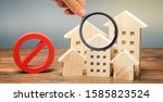 Small photo of Wooden houses and a prohibition sign. Inaccessible and expensive housing. Restrictions and a ban on the construction of buildings. Interdictions within settlements. Inaccessibility Index