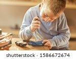 Young Boy Tinkering With Toys...