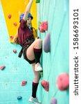 Small photo of High school student climbing rock climbing wall