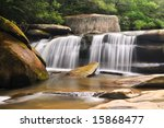 Western North Carolina landscape shot of a milky waterfall with rocks and forest. - stock photo