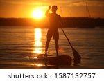 Teenage Boy Paddle Boarding On...