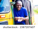 Small photo of young black African tricycle driver sitting inside his vehicle counting money