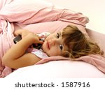 Little girl tucked into bed, holding a book - stock photo