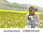 Woman Sneezing With Tissue In...