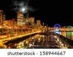 Seattle night view of the illuminated waterfront and skyline under a full moon breaking through clouds - stock photo
