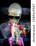 Small photo of The skeleton wears a suit with Sunglasses and lifting your hands and worship with lace a red rose flower at a suit shirt, Concept Death is an inevitable escape