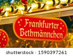 """Small photo of Red sign on a christmas market with yellow letters and the words """"Frankfurter Bethmannchen"""", (translation: """"Little Bethmann from Frankfurt""""), a marzipan-based treats that originate from Frankfurt"""