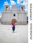 Small photo of Cajola, Quetzaltenango, Guatemala, June 30, 2019, Catholic Church and Sanctuary of the Holy Child of the Cross, with the indigenous and repressive woman of the Mayan people Mam, wearing her typical ty