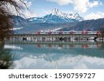 Two trains passing each other on a bridge over Inn River on a winter day with snowy Wilder Kaiser Mountains towering in background & reflected in the water in Langkampfen near Kufstein, Tyrol, Austria