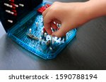 Girl playing in the Board game battleship, toy war ships and submarine. Selective focus.