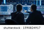 Small photo of Two Professional IT Programers Discussing Blockchain Data Network Architecture Design and Development Shown on Desktop Computer Display. Working Data Center Technical Department with Server Racks