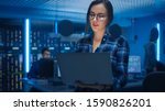 Small photo of Portrait of a Smart Seductive Young Woman Wearing Glasses Holds Laptop. In the Background Technical Department Office with Specialists Working and Functional Data Server Racks