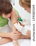 Health care professional taking care of a little boy leg injury - closeup - stock photo