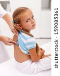 Little girl at the doctor for an examination - being checked with a stethoscope - stock photo