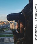 Small photo of Man in Military Uniform Looks through Binoculars at the City at Sunset