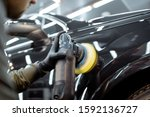 Worker polishing vehicle body with special grinder and wax from scratches at the car service station. Professional car detailing and maintenance concept - stock photo