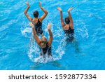 Synchronized swimming girls underwater dance action routine overhead pool photo.
