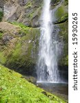 This is Multnomah WaterFall Upper Pool Plunging mist into pool over green hill after a 542 foot drop - stock photo