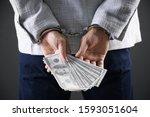 Man In Handcuffs Holding Bribe...