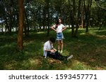 Small photo of A girl's dissatisfied while her boyfriend has to do the job during their dating in a wood on vacation.