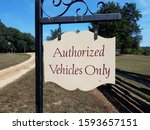Small photo of authorized vehicles only sign with wood fence and grass