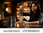 Small photo of Female bartender with black hair stirring ice with a bar spoon
