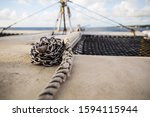 Small photo of Chain wrapped around a cleat used to weigh down a section of rope on a catamaran sailing in the Caribbean
