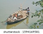 Small photo of Budge Budge, West Bengal, 01/15/2019: An Indian boatman standing on an overloaded wooden boat, with collected sediment/soil from Ganges riverbed ... near embankment.