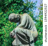 Stone Statue Of A Grieving And...