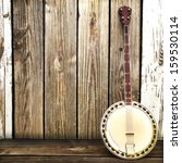 A Banjo Leaning On A Wooden...