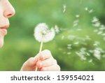 A Woman Blowing On A Dandelion...