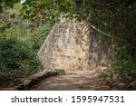 Small photo of section of the ancient stone wall of the historic hydroelectric power plant on the hermon stream trail in israel surrounded by dense semitropical vegetation