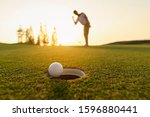 Small photo of lifestyle, golf, activity, outdoor, sport, golfer concept. Golf balls that are going to be hole by golfers at the green grass golf course at sunset.