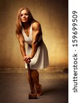 Young woman bodybuilder with hammer. Ancient style. - stock photo