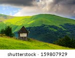 an abandoned building on the lawn on a background of mountains and stormy sky - stock photo