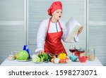 Small photo of Helpful culinary book. Woman chef cooking food. Culinary concept. Amateur cook read book recipes. Girl learn recipe. Book by famous chef. Improve cooking skill. Book recipes. According to recipe.