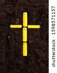 Small photo of Yellow batteries in the form of a cross in the soil. Environmental damage and pollution. Land contamination and destruction. Subsequent proper recycling and disposal.