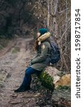 Small photo of Tired lonely young tourist girl with backpack is sitting on old tree near forest road and thinking whether go further. Single travel woman looks sideways and rests. Respite on forest trail