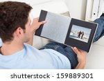 young man sitting on couch... | Shutterstock . vector #159889301