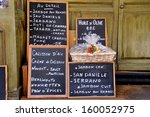Advertisement board at a French grocery.The text tells the people in French that they sell various kinds of ham, oil and other things. - stock photo