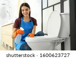 Young Woman Cleaning Toilet...