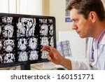 Stock photo doctor examining an mri scan of the brain on monitior 160151771