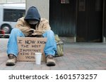 Depressed Panhandler Sitting With A Cup And Sign