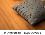 Small photo of Grey pincushion with colorful pins and needles on an oak table.