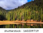 Mountain lake and colorful foliage in Autumn coniferous forest - stock photo