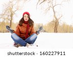 Young girl in lotus pose in the snow - stock photo
